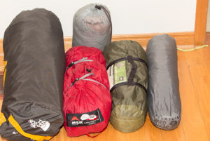 From left to right. North Face Mountain 25, MSR Hubba Hubba NX, REI quarter dome, Mountain Hardware Super Mega UL. Behind: MEC Guide Tarp